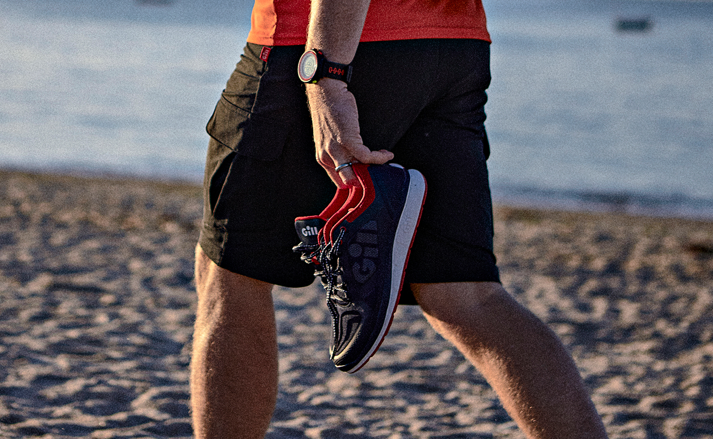 man carrying shoes on beach